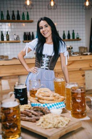 Photo pour Belle jeune serveuse dans la main traditionnelle de fixation de costume allemand sur la hanche et souriant à l'appareil-photo - image libre de droit