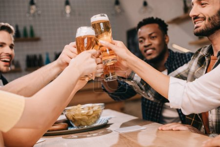 Photo pour Vue partielle des amis multiculturels joyeux clinking des verres avec la bière de lager dans le pub - image libre de droit