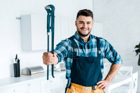 Photo for Selective focus cheerful handyman in uniform standing with hand on hip and holding wire cutters - Royalty Free Image
