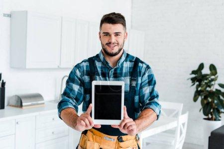 Photo pour Heureux bricoleur tenant tablette numérique avec écran blanc - image libre de droit