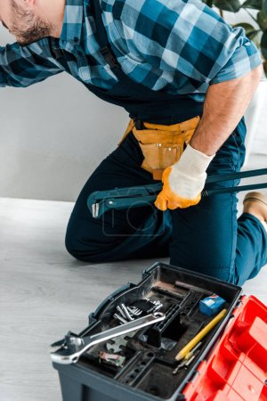 Photo for Cropped view of handyman working near kitchen cabinet and toolbox with instruments - Royalty Free Image
