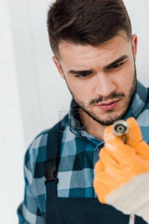Photo pour Foyer sélectif du réparateur en gant de caoutchouc regardant tuyau métallique - image libre de droit