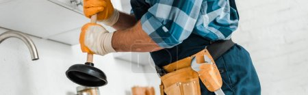 Photo for Panoramic shot of handyman with tool belt holding plunger in kitchen - Royalty Free Image