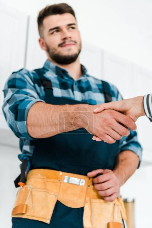 Photo for Selective focus of woman shaking hands with handyman - Royalty Free Image