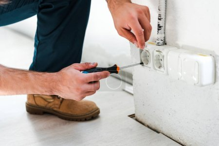 Photo for Cropped view of repairman sitting while fixing power - Royalty Free Image
