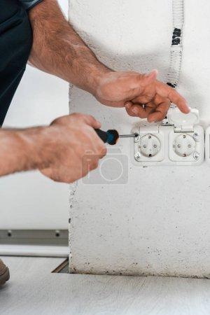 Photo pour Vue recadrée du technicien retenant le tournevis près de la prise de courant - image libre de droit