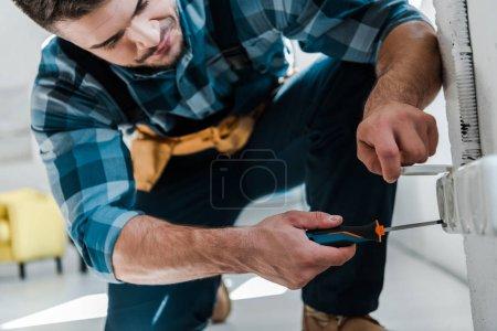 Photo pour Réparateur barbu dans l'uniforme se reposant tout en fixant la prise de puissance avec le tournevis - image libre de droit