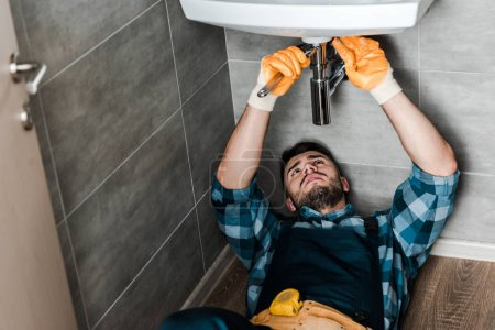Photo for Selective focus of repairman fixing water damage with wrench in bathroom - Royalty Free Image