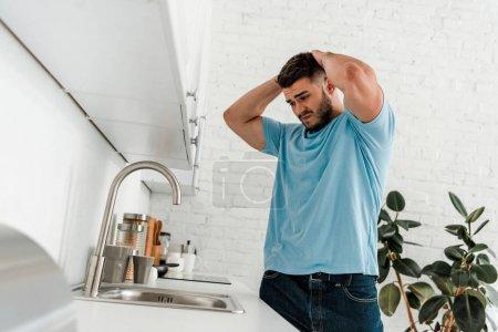 Photo pour Foyer sélectif de l'homme bouleversé regardant évier dans la cuisine moderne - image libre de droit