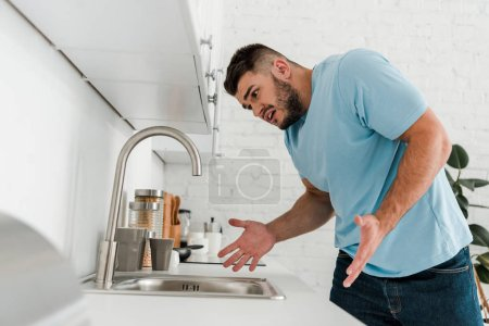 Photo for Selective focus of upset man gesturing while looking at sink in modern kitchen - Royalty Free Image
