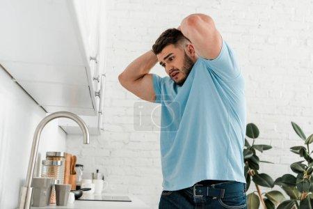 Photo pour Homme stressé touchant la tête tout en regardant évier dans la cuisine moderne - image libre de droit
