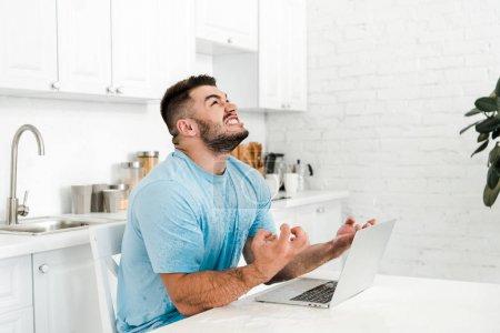 Photo pour Homme émotionnel gestuelle tout en regardant vers le haut près de l'ordinateur portable dans la cuisine - image libre de droit