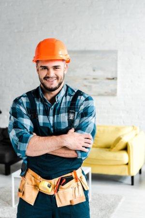 Photo pour Travailleur heureux dans le casque de sécurité regardant la caméra tout en se tenant avec les bras croisés - image libre de droit