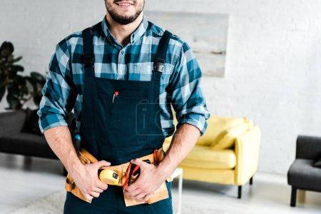 Photo pour Vue recadrée du travailleur heureux touchant ceinture d'outils dans le salon - image libre de droit
