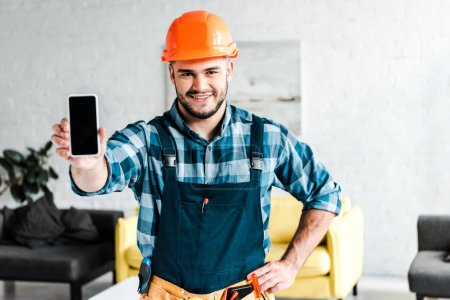 happy worker holding smartphone with blank screen and standing with hand on hip