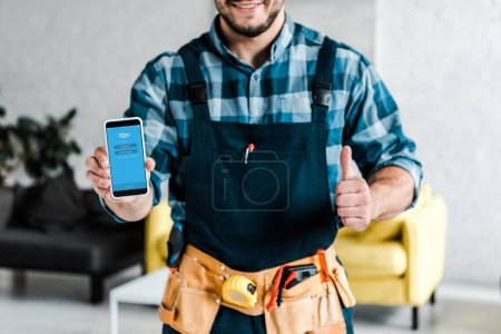 KYIV, UKRAINE - JULY 31, 2019: cropped view of happy man holding smartphone with skype app on screen and showing thumb up