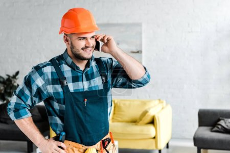 cheerful worker in safety helmet talking on smartphone while standing with hand on hip
