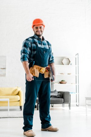 Photo for Happy bearded worker in safety helmet holding clipboard in living room - Royalty Free Image