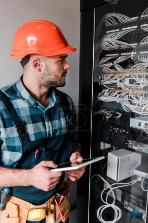 Photo for Handsome bearded workman holding digital tablet and looking at wires and cables - Royalty Free Image