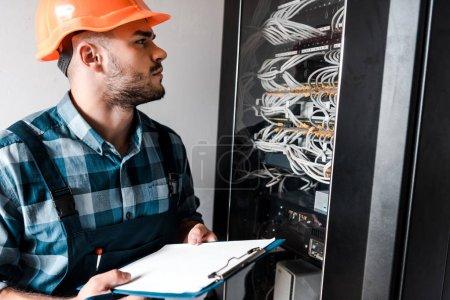 Techniker im Schutzhelm hält Klemmbrett, während er Drähte und Kabel betrachtet