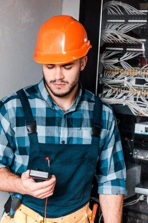 Photo pour Beau technicien barbu tenant le compteur numérique près des fils et des câbles - image libre de droit