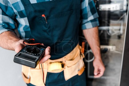 Photo pour Vue recadrée du technicien retenant le compteur numérique près des fils et des câbles - image libre de droit