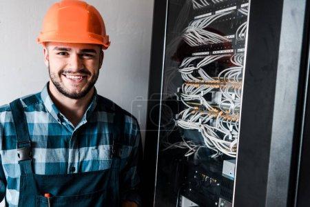 Photo pour Technicien heureux regardant la caméra près des fils et des câbles - image libre de droit