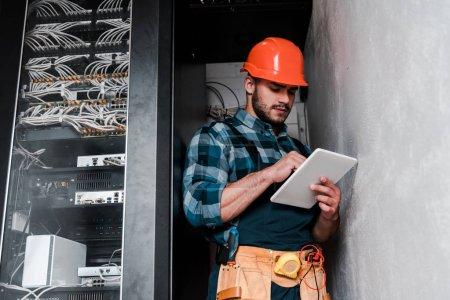Photo for Handsome bearded technician in safety helmet holding digital tablet - Royalty Free Image