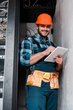 Photo for Happy bearded technician in safety helmet using digital tablet - Royalty Free Image