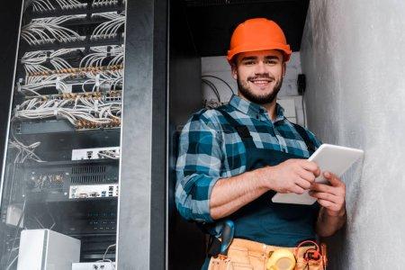 Photo pour Technicien barbu heureux dans le casque de sécurité retenant la tablette numérique - image libre de droit
