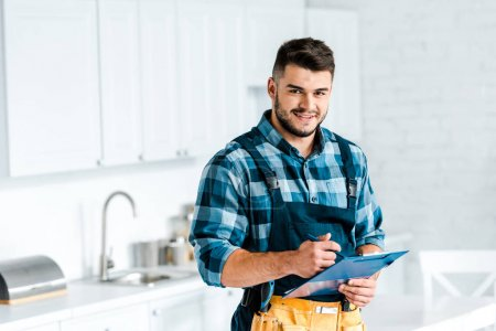 Photo for Happy bearded workman holding clipboard and looking at camera in kitchen - Royalty Free Image