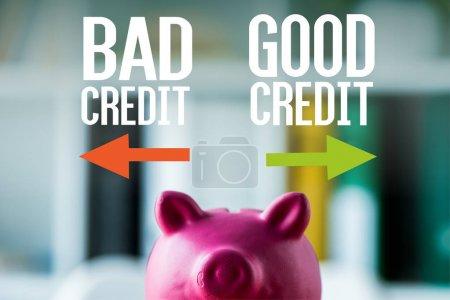 Foto de Alcancía rosa en escritorio de madera cerca de mal crédito, letras de buen crédito en la oficina - Imagen libre de derechos