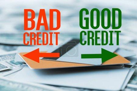 Photo pour Focus sélectif de la pile avec des cartes de crédit près de mauvais crédit, bon lettrage de crédit sur les billets en dollars - image libre de droit
