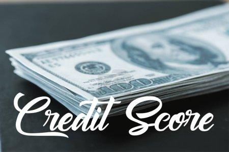 Foto de Enfoque selectivo de la pila con billetes de dólar cerca de las letras de puntuación de crédito en negro - Imagen libre de derechos