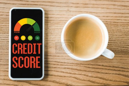 Photo for Top view of smartphone with credit score lettering on screen near cup of coffee on table - Royalty Free Image