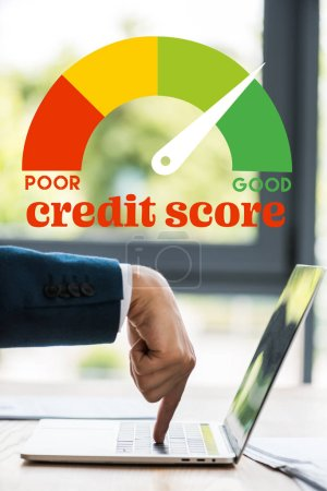 Photo for Cropped view of businessman pointing with finger at laptop keyboard near credit score letters - Royalty Free Image