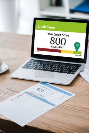 Photo for Laptop with your credit score letters on screen near paper with credit report on desk - Royalty Free Image