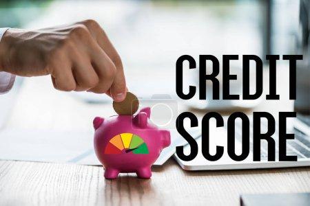Photo pour Vue recadrée de l'homme d'affaires mettant la pièce de monnaie dans la tirelire rose près du lettrage et de l'ordinateur portatif de pointage de crédit - image libre de droit