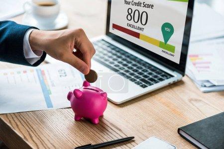 Photo pour Vue recadrée de l'homme d'affaires mettant la pièce de monnaie dans la tirelire rose près de l'ordinateur portatif avec vos lettres de pointage de crédit - image libre de droit