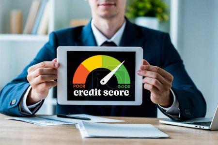 Photo for Selective focus of happy man holding digital tablet with credit score lettering in office - Royalty Free Image