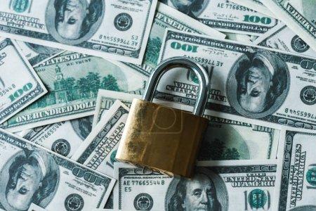 Photo pour Vue du haut du cadenas métallique sur des billets de banque en dollars - image libre de droit