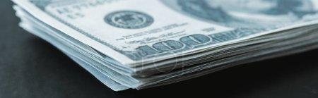 Photo pour Plan panoramique de pile avec billets en dollars sur noir - image libre de droit