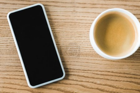 top view of smartphone with blank screen near cup of coffee