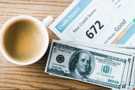 Photo pour Vue supérieure de tasse avec le café près du papier avec le lettrage de rapport de crédit sur le papier et les billets de banque de dollar - image libre de droit
