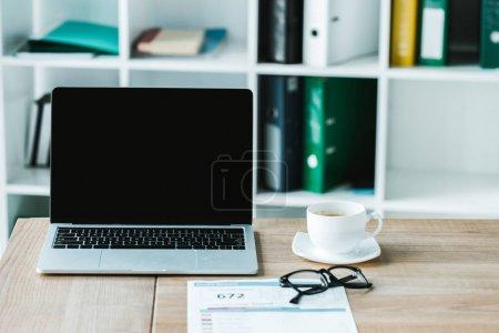 Photo pour Tasse de café près des glaces et de l'ordinateur portatif avec l'écran blanc sur la table - image libre de droit