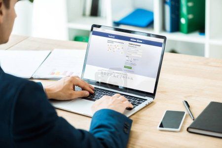 kyiv, Ukraine - 8. Juli 2019: Mann tippt auf Laptop mit Facebook-Website in der Nähe Smartphone mit leerem Bildschirm auf Tisch