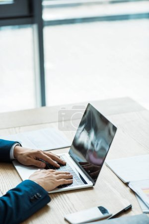 Photo for Cropped view of man typing on laptop near smartphone with blank screen - Royalty Free Image