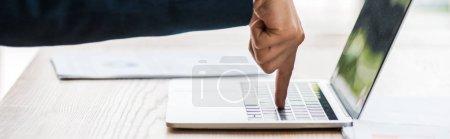 Photo pour Prise de vue panoramique de l'homme pointant du doigt au clavier de l'ordinateur portable - image libre de droit