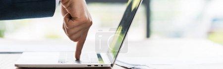 Photo pour Plan panoramique de l'homme d'affaires pointant avec le doigt au clavier de l'ordinateur portable - image libre de droit