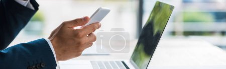 Photo for Panoramic shot of man holding smartphone near laptop - Royalty Free Image